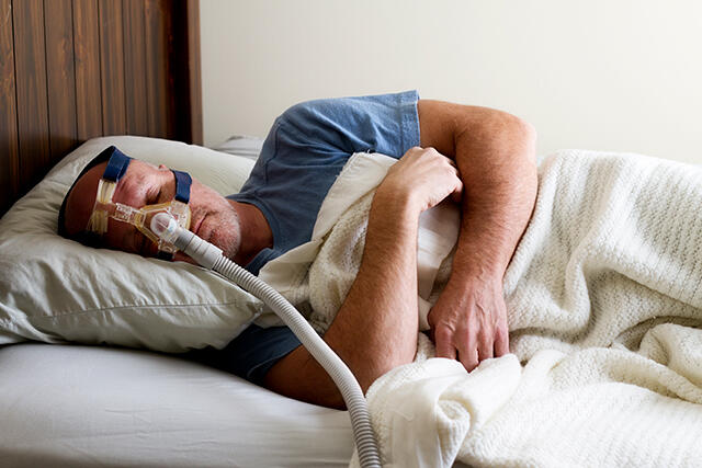 man sleeping while using a CPAP device