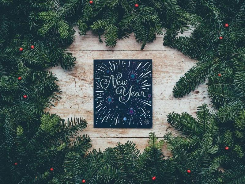 wreath surrounding a New Year sign on top of a wooden background