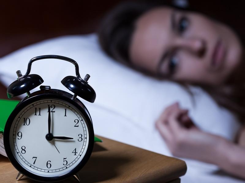 Woman unable to fall asleep looking at clock