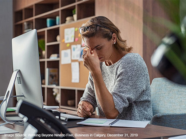 business woman with headache in front of her computer