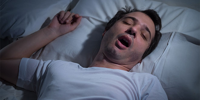 Man with sleep apnea snoring in bed